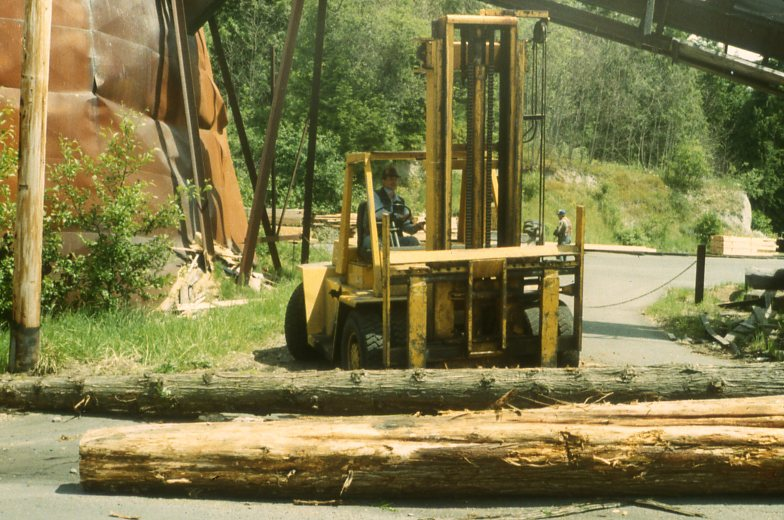 Danny Waterman moving Cedar logs for pick up by Bradley Construction.