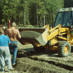 Pete Krogseng – backhoe, Jim & Ryan Porter placing pea gravel in the drainage trenches.